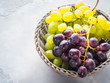 White and dark grapes in a basket on gray. Abstract minimal fruit still life - 208375089