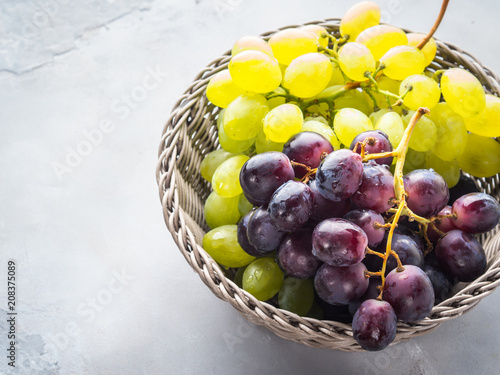 White and dark grapes in a basket on gray. Abstract minimal fruit still life