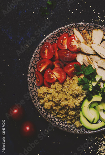 Foto Murales Healthy food, avocado, quinoa, chicken and tomatoes on plate, top view