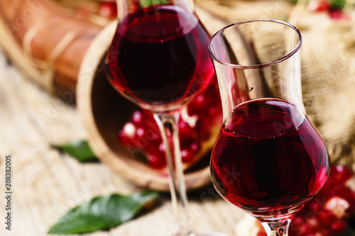Homemade pomegranate liqueur, still life in rustic style, old wooden background, selective focus