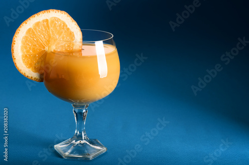 Fotobehang Sap Orange juice in a glass with orange wedge on side on blue background