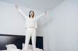 Leinwanddruck Bild - joyful young girl in white pajamas jumping on the bed early in the morning, under the eyes white patches