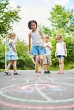 Mädchen und Freunde spielen ein Hüpfspiel - 208392693