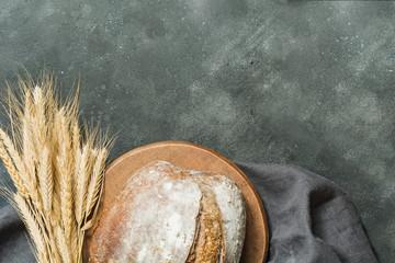 Homemade fresh rye bread on dark board. Close up. Copy space.