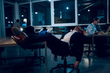 Tired man sleeping in office after overworking. Exhausted businessman sleeping in his office chair with his legs up on office table in middle of night. - 208402822