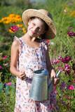 girl with metal watering can in summer garden - 208403294