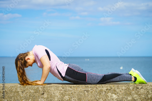 Fotobehang School de yoga Woman doing yoga next to sea