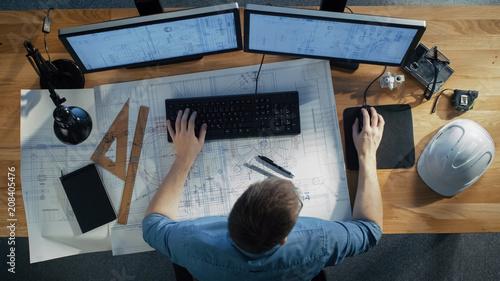 Widok z góry inżyniera architekta pracuje nad jego plany, trzymając komputer typu Tablet, przy użyciu komputera stacjonarnego również. Jego biurko jest pełne przydatnych przedmiotów i wieczornego słońca.