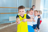 Children and recreation, group of happy multiethnic school kids playing tug-of-war with rope in gym - 208418023