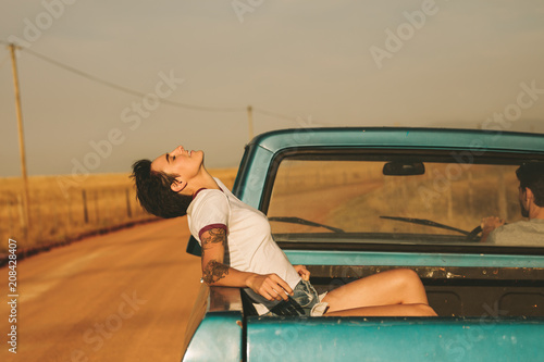 Foto Murales Couple enjoying the road trip in their car