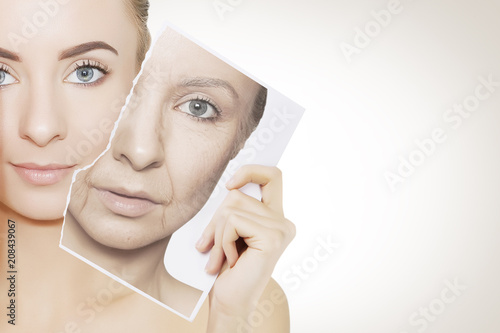 Foto Murales portrait of young woman face holding portrait with old wrinkled face
