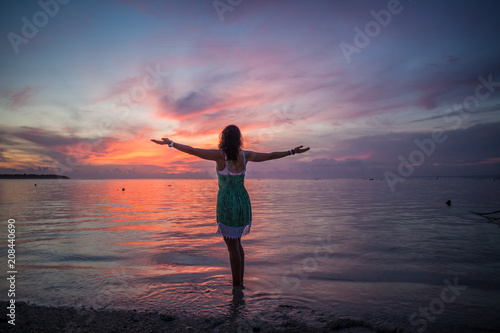 Aluminium Strand Woman at a Pink and Purple Ocean Sunset with Arms Outstretched