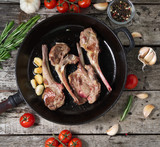 Roasted lamb ribs with rosemary, tomatoes and garlic on pan on dark old rustic wooden background, top view - 208441270