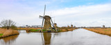 Traditional Dutch windmills near the water canals with beautiful white clouds and blue sky reflecting in water. UNESCO world heritage sight in Kinderdijk, Netherlands in winter