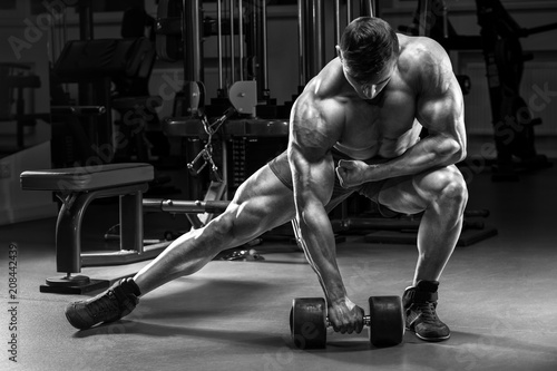 Poster Muscular man in gym working out. Strong male bodybuilder