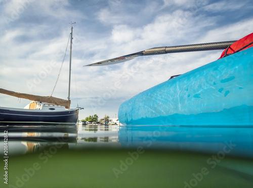 Stand up paddleboard and sailboat