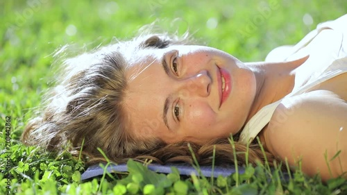 Young smiling woman face in grass