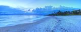 Sunset over ocean on Naples Beach with dark skies overhead