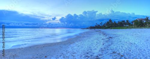 Aluminium Strand Sunset over ocean on Naples Beach with dark skies overhead