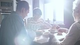PAN of family eating breakfast in morning: cheerful woman cutting pie and giving pieces to senior lady and young man with ponytail - 208460416