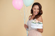 Cheerful emotional attractive young woman wearing outfit in pastel colors holding bunch of balloons and birthday cake with flowers while winking at camera against beige background.