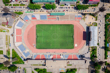 Aerial photography of a modern  stadium with green field for football, a big road, city traffic and parks on a warm summer day. Helicopter drone shot