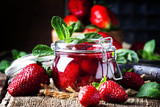 Strawberry confiture with whole berries, vintage wooden background, selective focus - 208477638