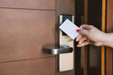 Young woman opening hotel room electronic lock with key card - 208481204
