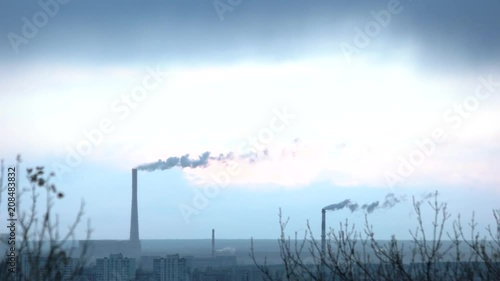 Two huge steaming plant power plant tubes over blue sky. Urban industrial city with plants in eastern europe.