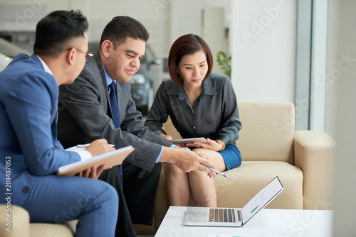 Middle-aged potential customer wearing classical suit looking through photos of new car models while having meeting with highly professional dealers at modern showroom