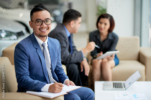 Poster Portrait shot of handsome Asian car dealer wearing elegant suit looking at camera with wide smile while distracted from working meeting at showroom