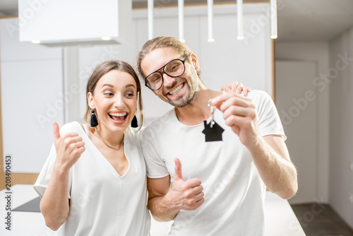 Portrait of a young and happy couple dressed in white t-shirts holding home keys indoors - 208490453
