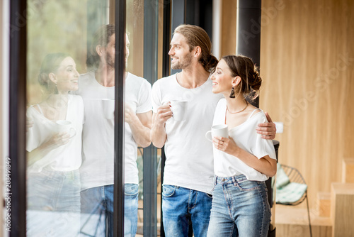 Foto Murales Young and happy couple dressed in white shirts standing together with cups near the window at home