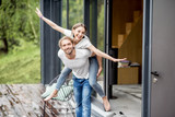 Happy lovely couple having fun playing together on the terrace outdoors of the modern house - 208492088