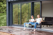 Leinwanddruck Bild - Young couple sitting with cups on the terrace of the modern house enjoying beautiful view outdoors