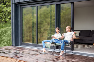 Young couple sitting with cups on the terrace of the modern house enjoying beautiful view outdoors