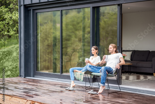 Leinwanddruck Bild Young couple sitting with cups on the terrace of the modern house enjoying beautiful view outdoors