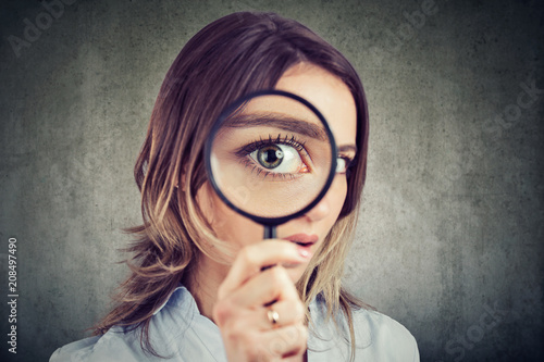 Leinwanddruck Bild Curious woman looking through a magnifying glass