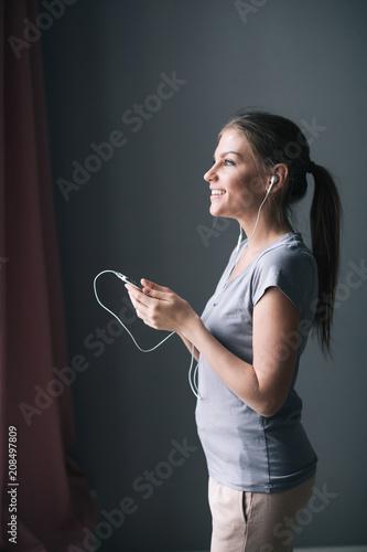 Fotobehang Muziek Smiling girl playing music using a smartphone and wearing headphones at home.