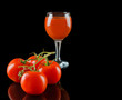 Tomato isolated on a black glossy background with realistic reflection and water drops