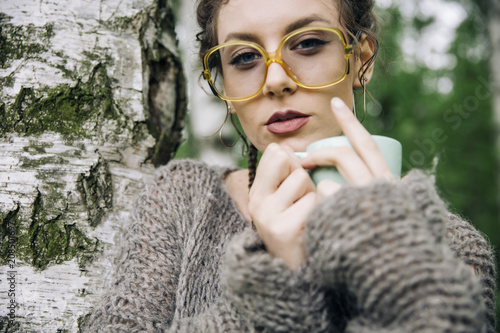 Young woman in a sweater and with glasses drinking coffee in the park