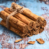 Bunch of fresh Indian cinnamon sticks on blue wooden table - 208506027