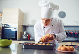A confectioner in uniform prepares cupcakes in the kitchen. - 208511468