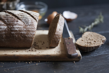 Sliced whole grain bread on wooden cutting board; selective focus background.