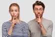 Leinwanddruck Bild - Amazed European female and male make silence sign, keep fore fingers on lips, tell secret and private information, isolated on white background. Surprised best friends gossip about something