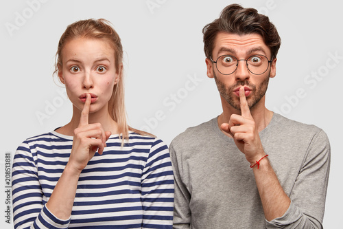 Leinwanddruck Bild Amazed European female and male make silence sign, keep fore fingers on lips, tell secret and private information, isolated on white background. Surprised best friends gossip about something