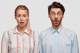 Portrait of stunned female and male colleagues have stupefied expressions, look with bated breath, being not ready to prepare deadline task, isolated over white background. People, cooperation concept - 208514042