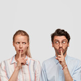 Indoor portrait of female and male spies hear private secret inforamtion, keep index fingers on lips, pose against white background with blank copy space for your advertisement or promotional text - 208514079
