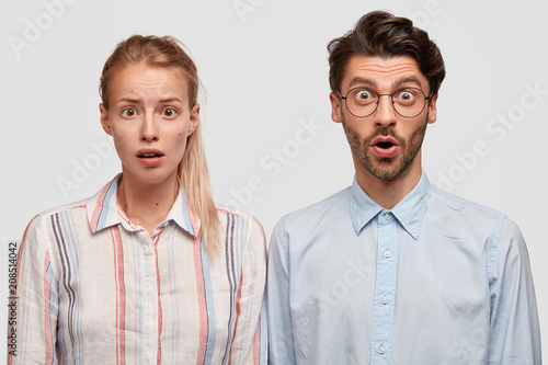 Leinwanddruck Bild Portrait of stunned female and male colleagues have stupefied expressions, look with bated breath, being not ready to prepare deadline task, isolated over white background. People, cooperation concept
