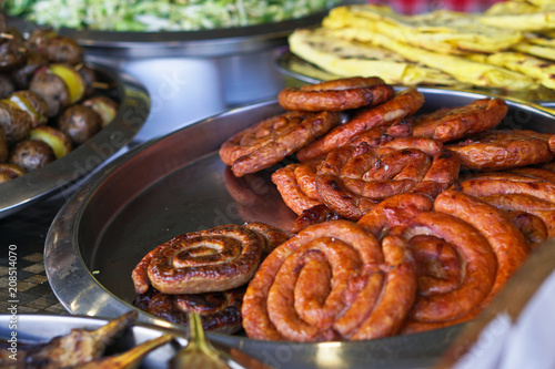 Grilled sausage on a grill with a delicious crust on the background of vegetables. Summer holidays and food in nature. Stock Photo
